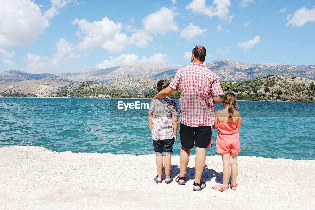 Rear View Of Father With Children Standing On Shore At Beach Against Sky