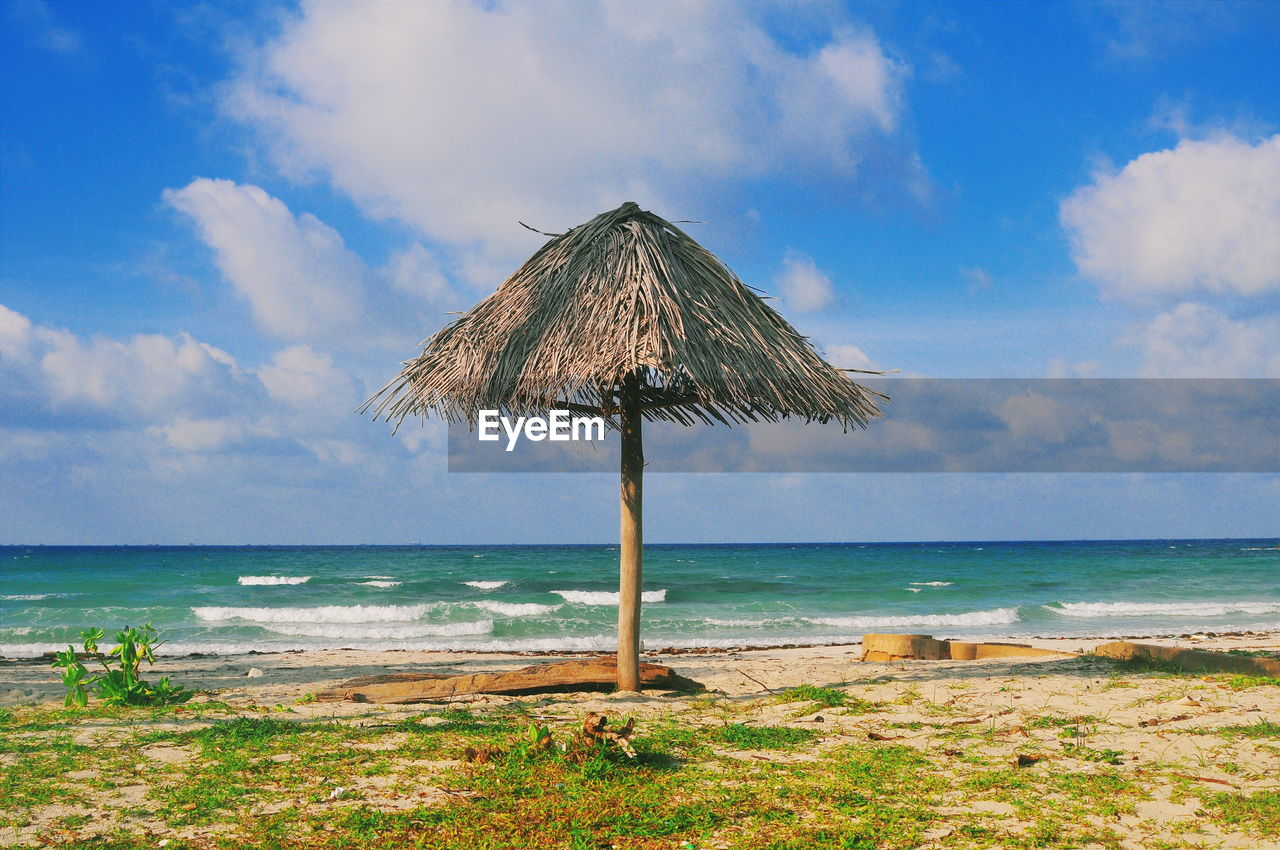 sea, water, horizon over water, beach, sky, land, horizon, scenics - nature, cloud - sky, beauty in nature, tranquil scene, thatched roof, tranquility, nature, day, roof, no people, outdoors, idyllic