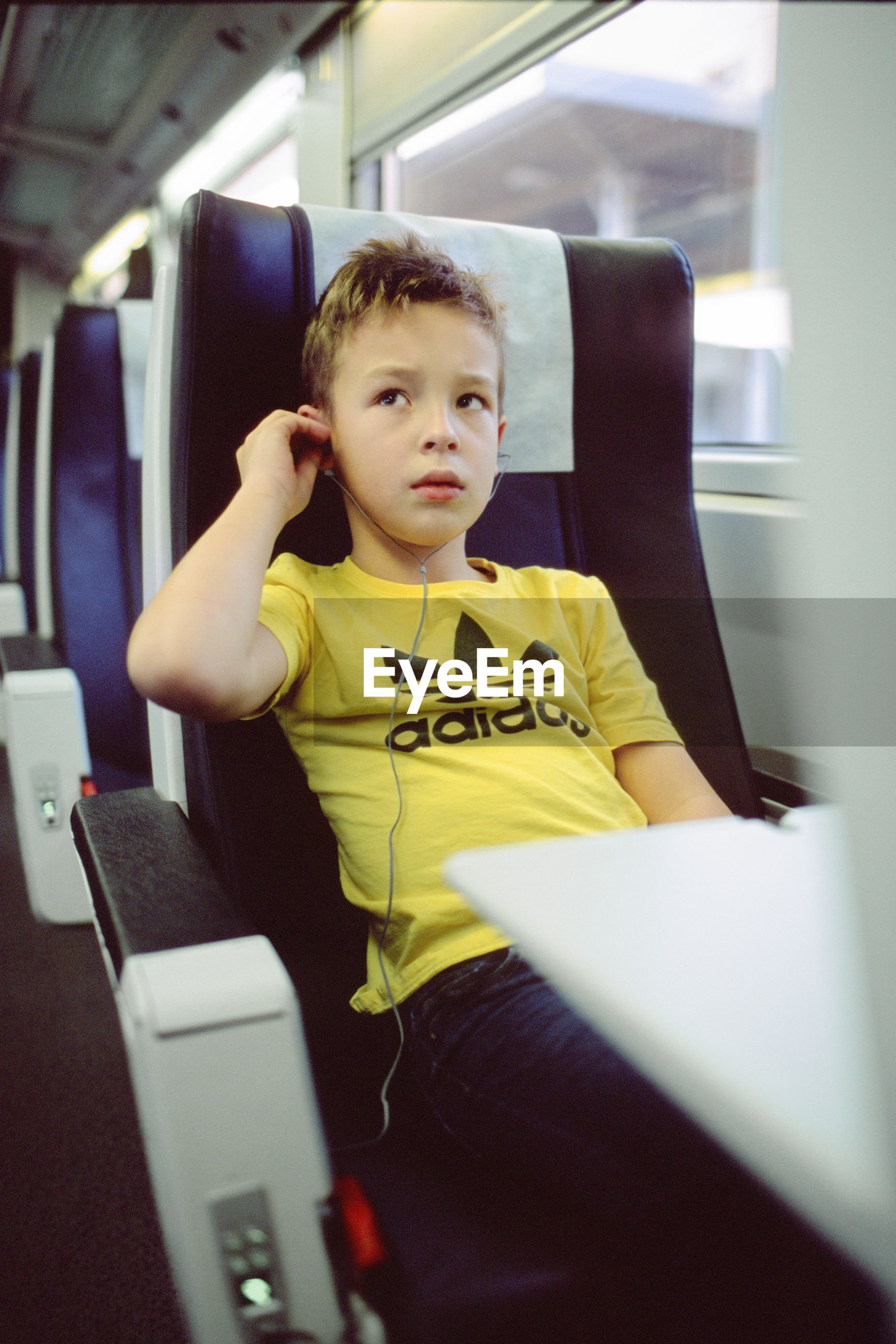 REAR VIEW OF BOY SITTING ON SEAT IN TRAIN