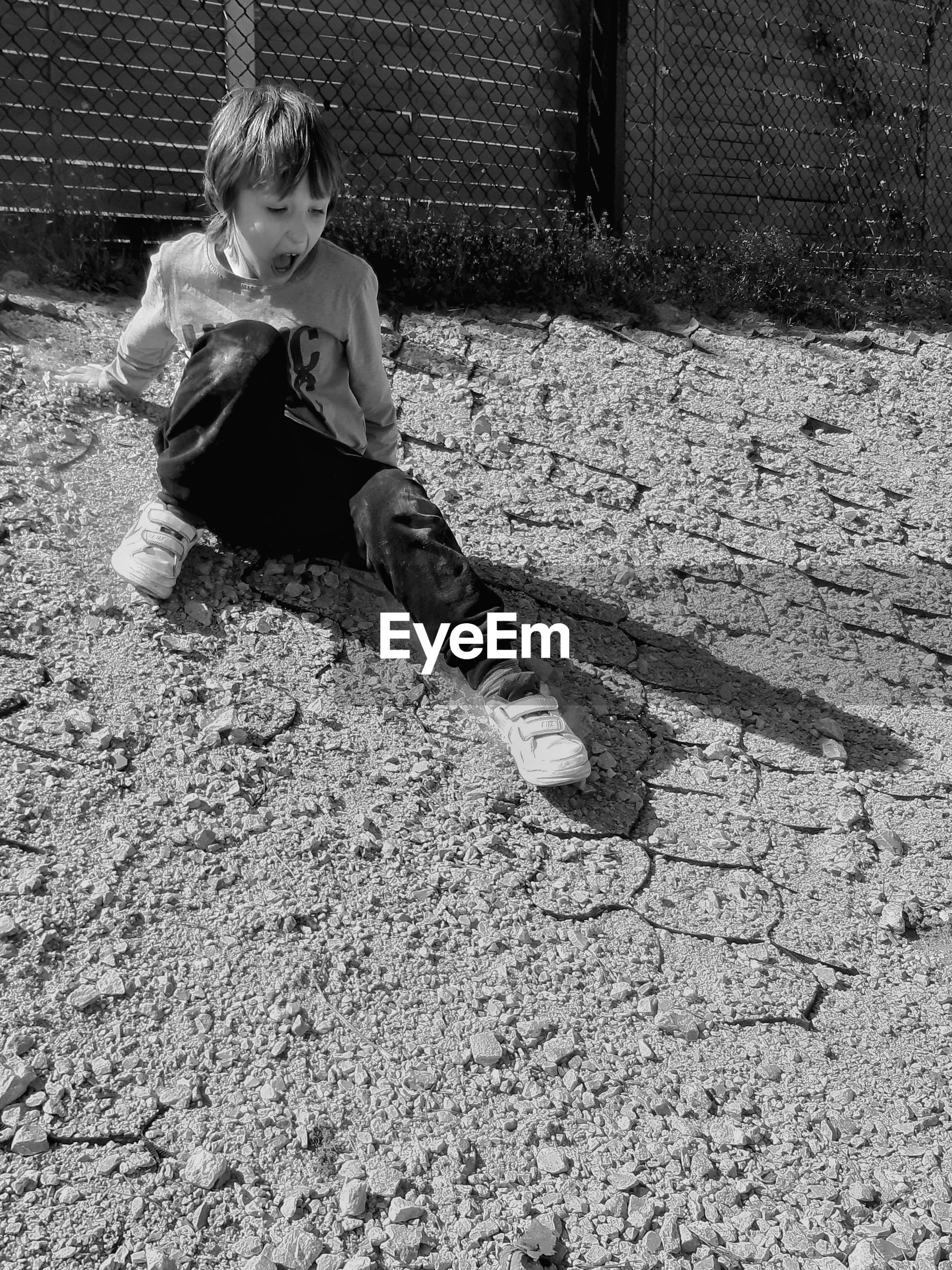 High angle view of boy sitting outdoors