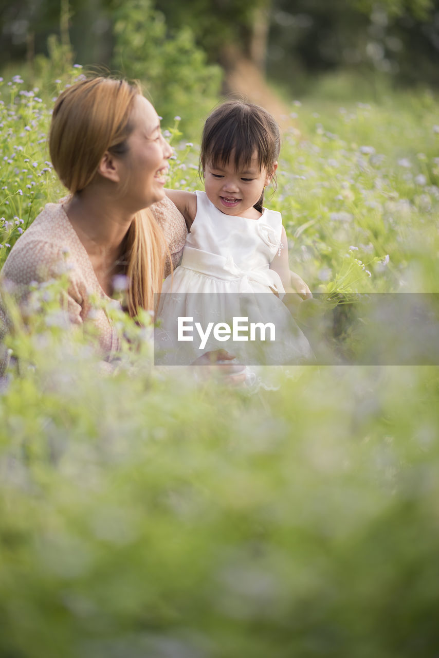 Smiling mother with daughter amidst plants