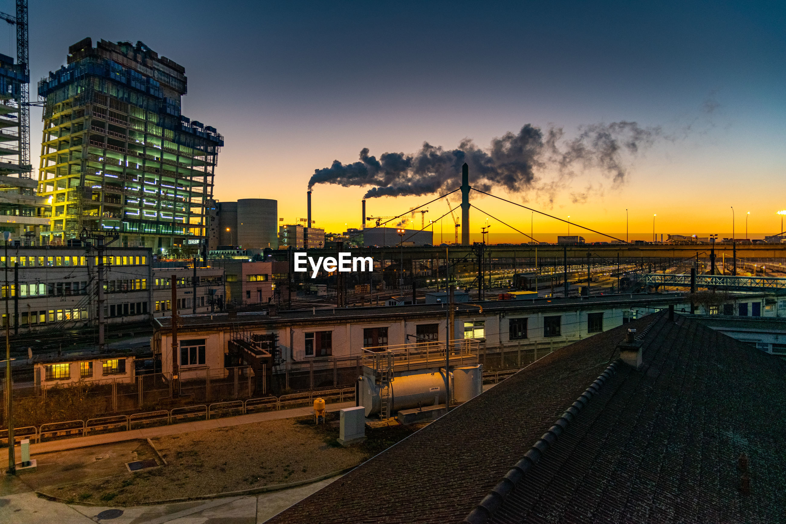 RAILROAD TRACKS BY BUILDINGS AGAINST SKY AT SUNSET