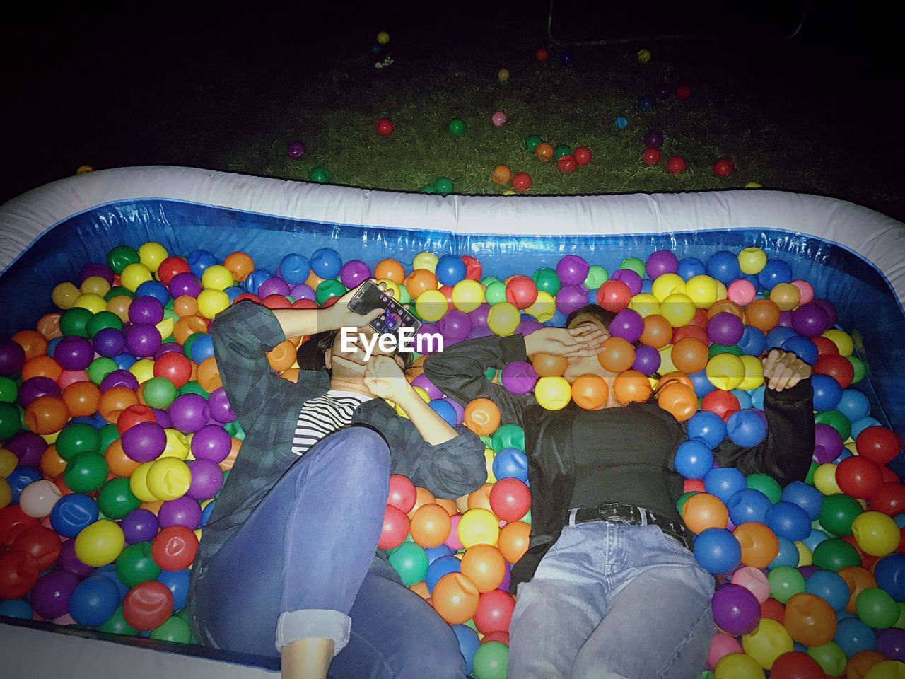 leisure activity, low section, real people, human leg, high angle view, multi colored, childhood, togetherness, barefoot, two people, fun, playing, human body part, lifestyles, water, floating on water, day, sitting, indoors