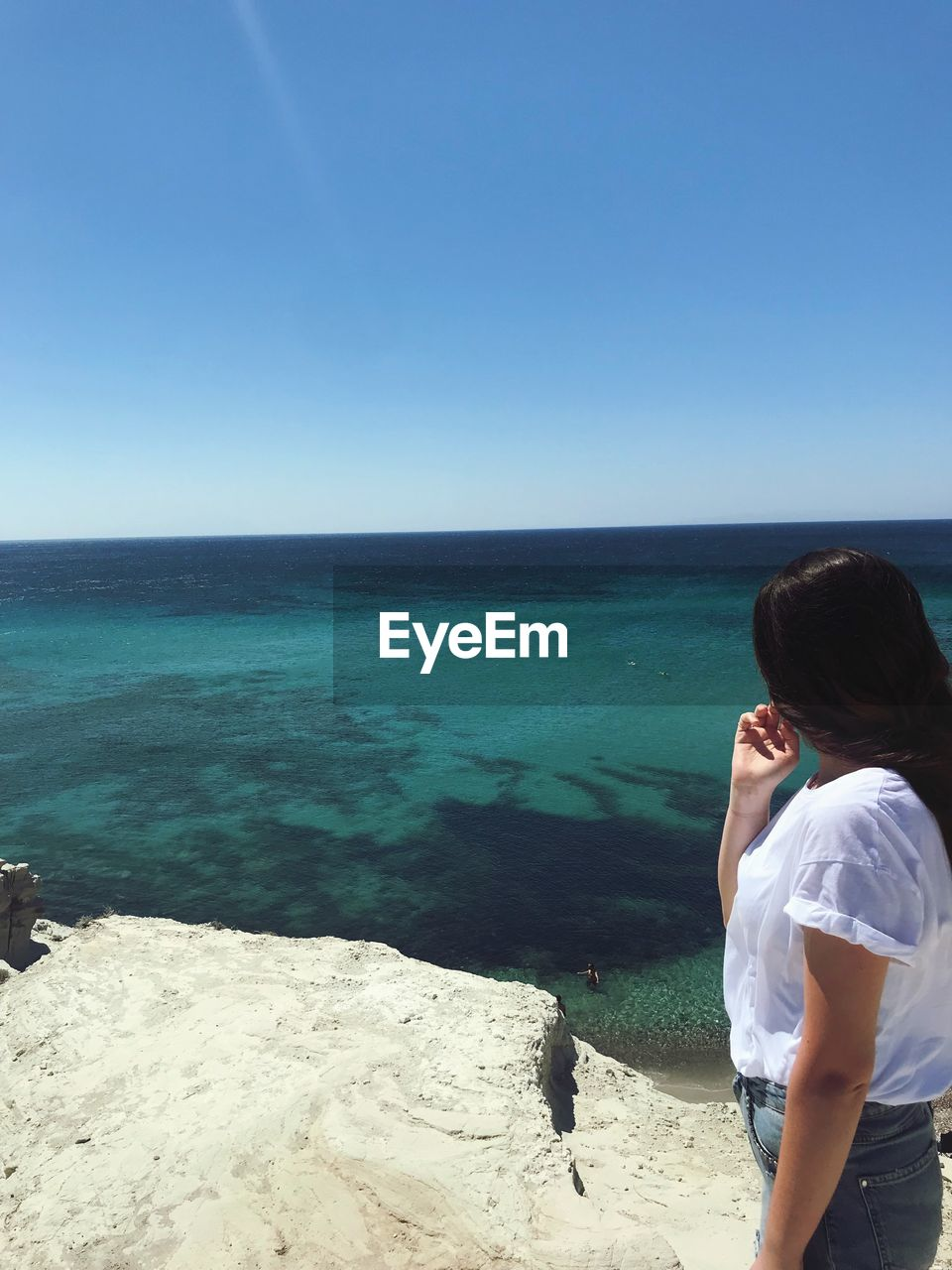 Side view of woman looking at sea against clear sky