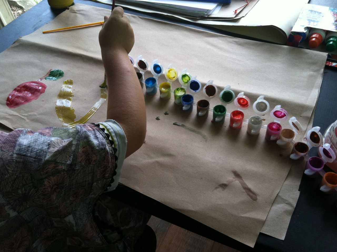 Cropped image of boy painting in paper on table at home