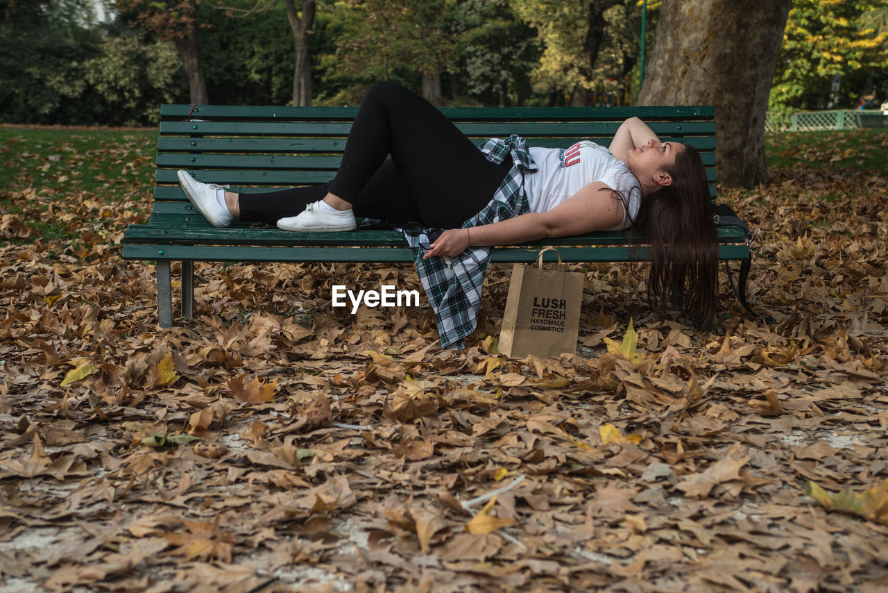 real people, one person, autumn, leaf, plant part, lifestyles, leisure activity, nature, casual clothing, day, bench, young adult, lying down, change, sitting, park, full length, relaxation, teenager, outdoors, leaves, contemplation, adolescence