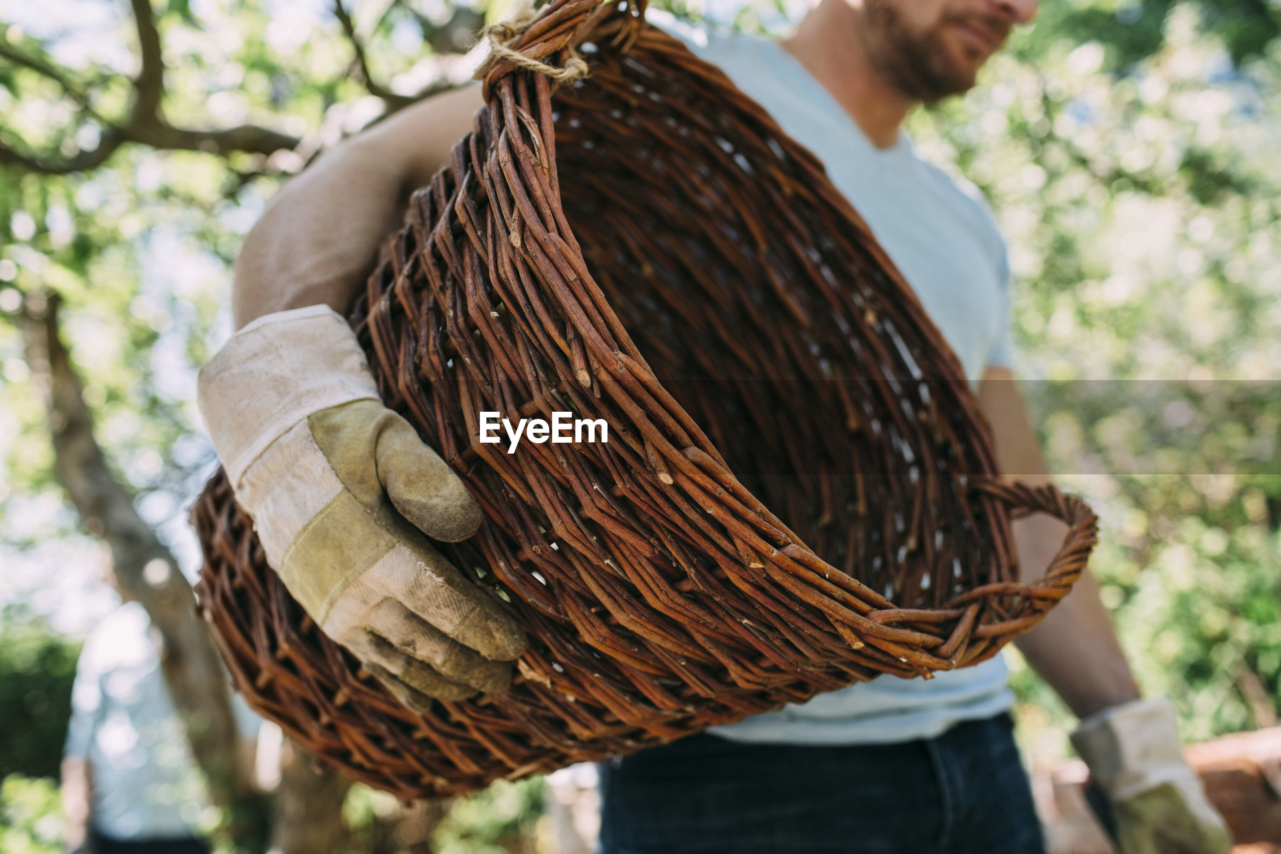 CLOSE-UP OF MAN HOLDING WICKER BASKET