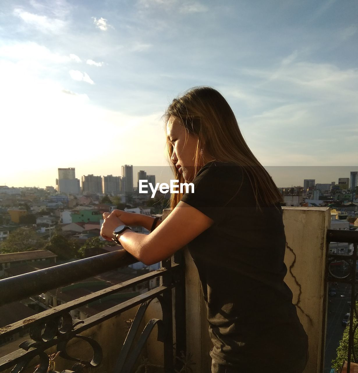 Side View Of Woman Standing At Balcony In City Against Sky During Sunset