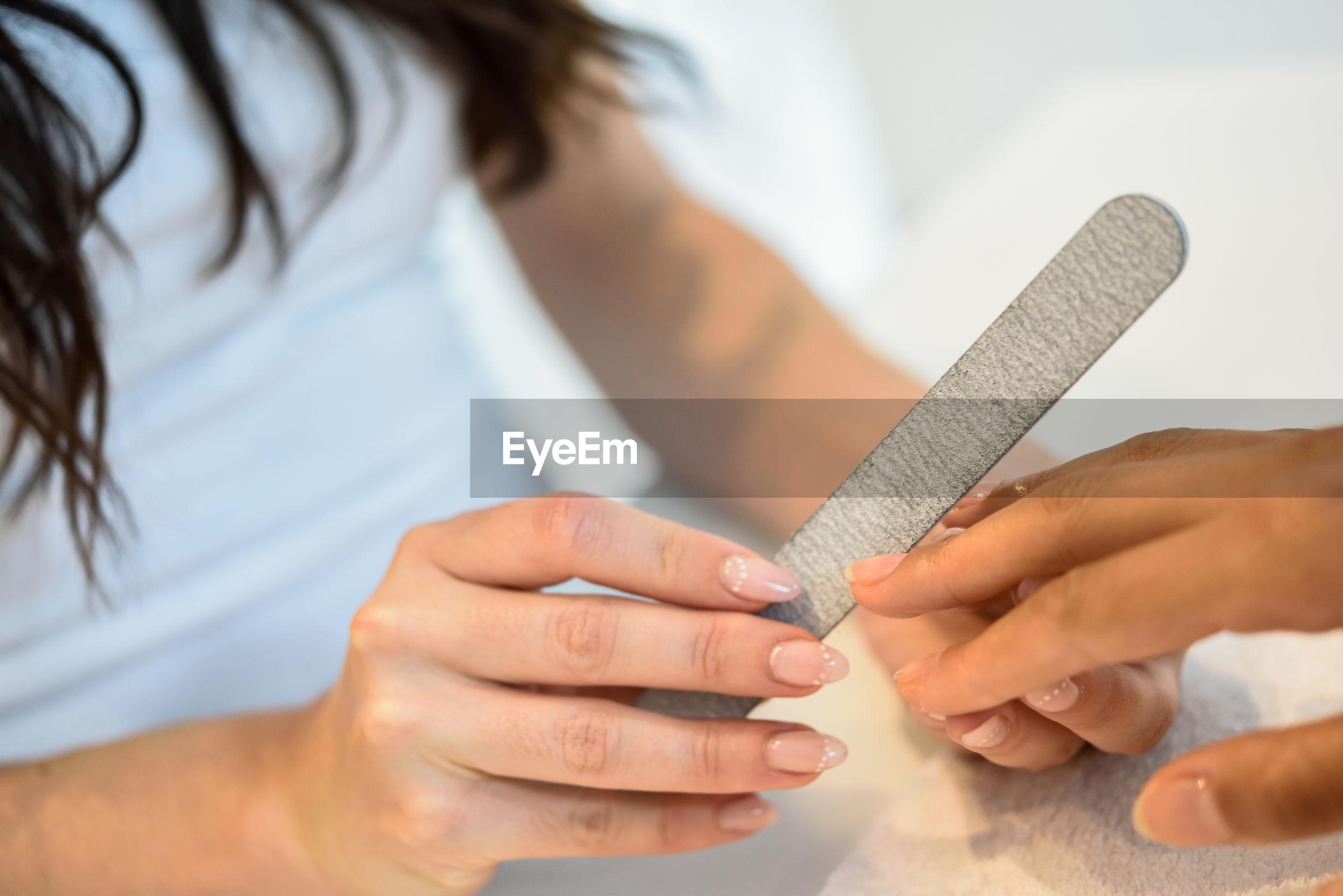 Midsection of woman filing fingernails at nail salon