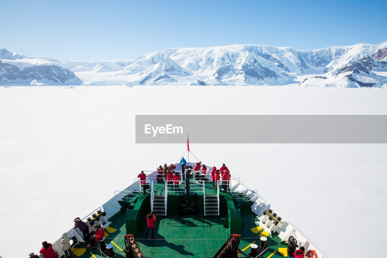 People On Cruise Ship By Snowcapped Mountain Against Sky
