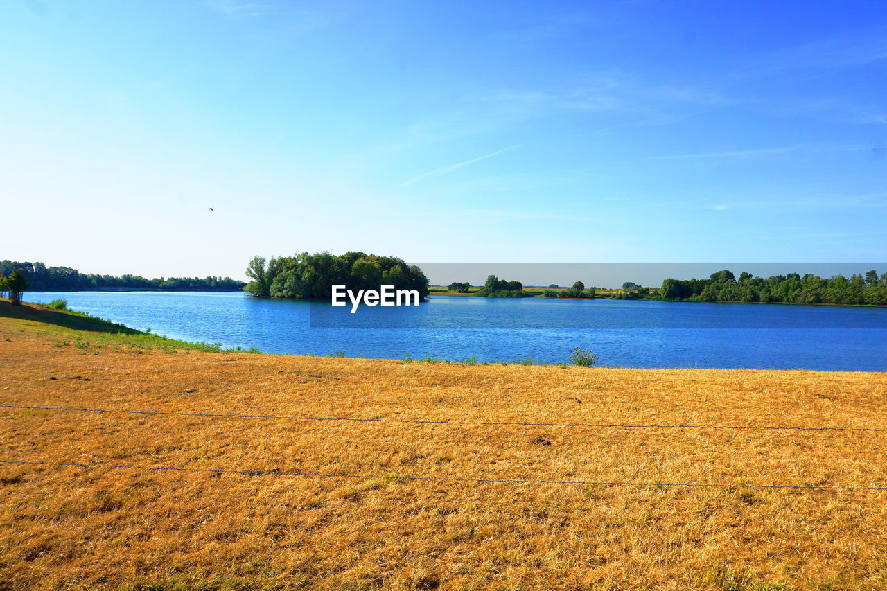 water, sky, scenics - nature, plant, tranquil scene, tranquility, beauty in nature, land, nature, blue, no people, grass, day, lake, tree, environment, landscape, non-urban scene, field, outdoors
