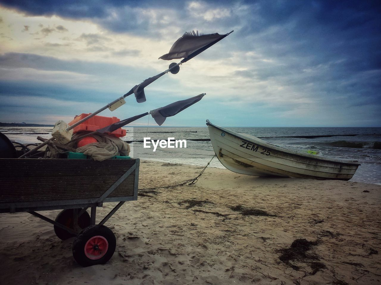 sea, beach, sand, sky, water, horizon over water, shore, transportation, nautical vessel, mode of transport, cloud - sky, nature, men, real people, one person, outdoors, day, scenics, beauty in nature, moored, full length, flying, one man only, people