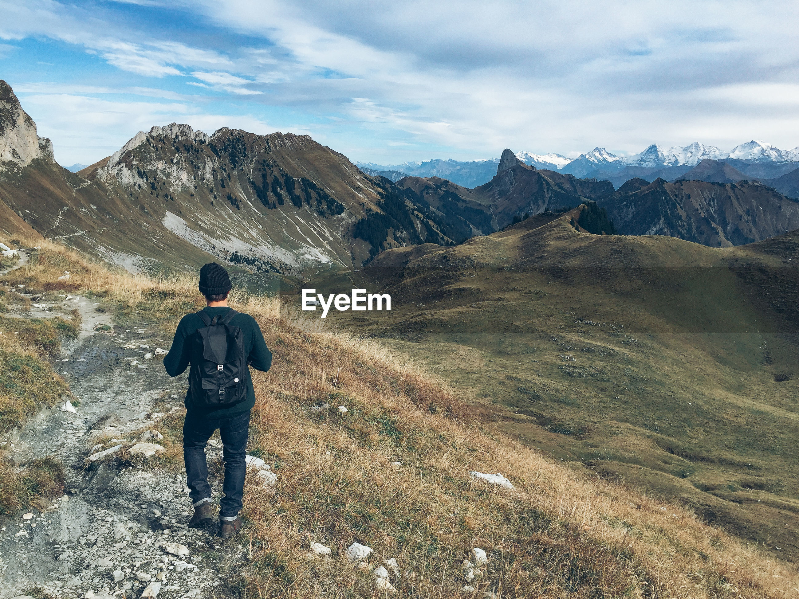Rear view of man walking on field by mountains