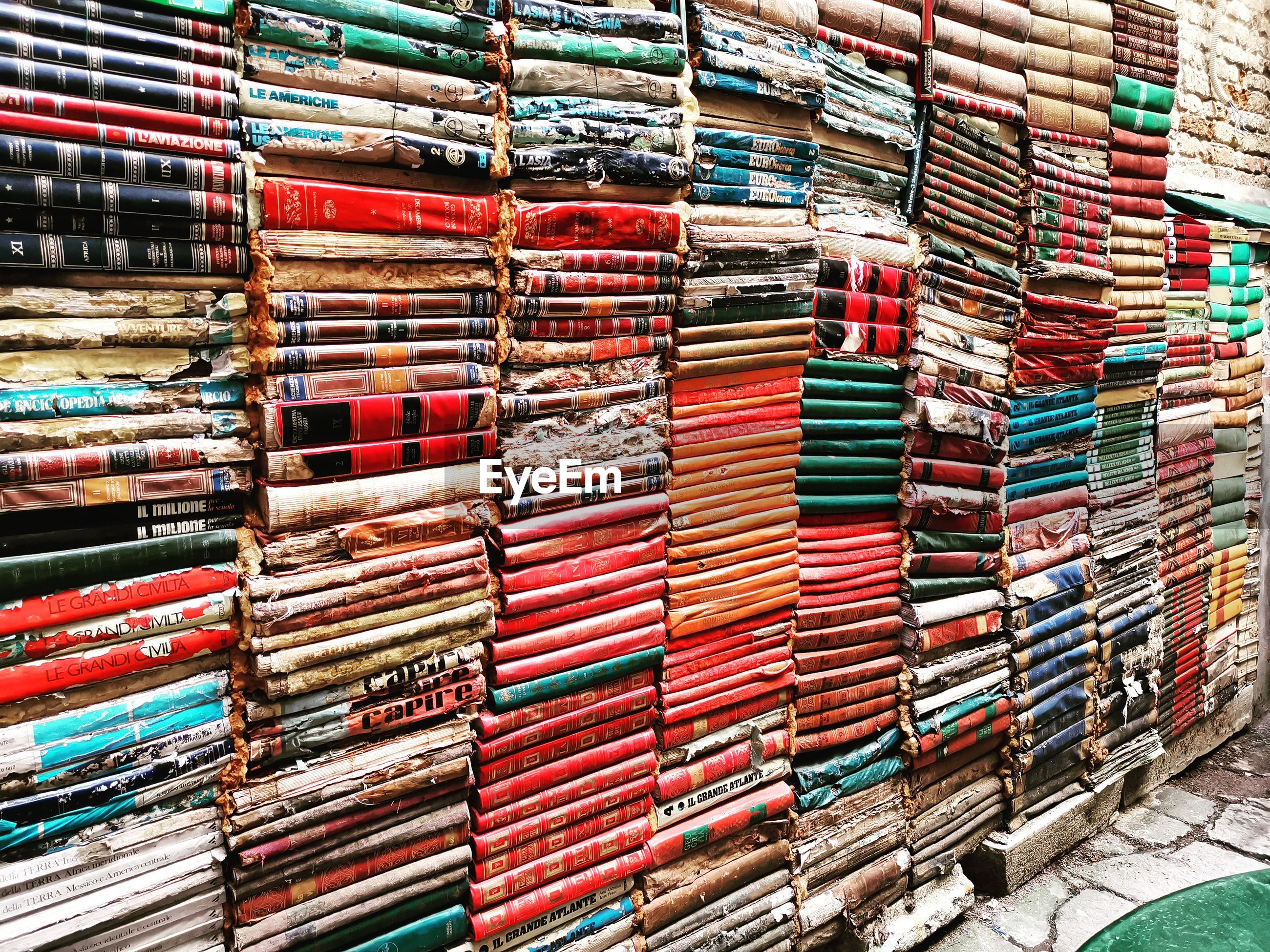 Old stacked books by wall