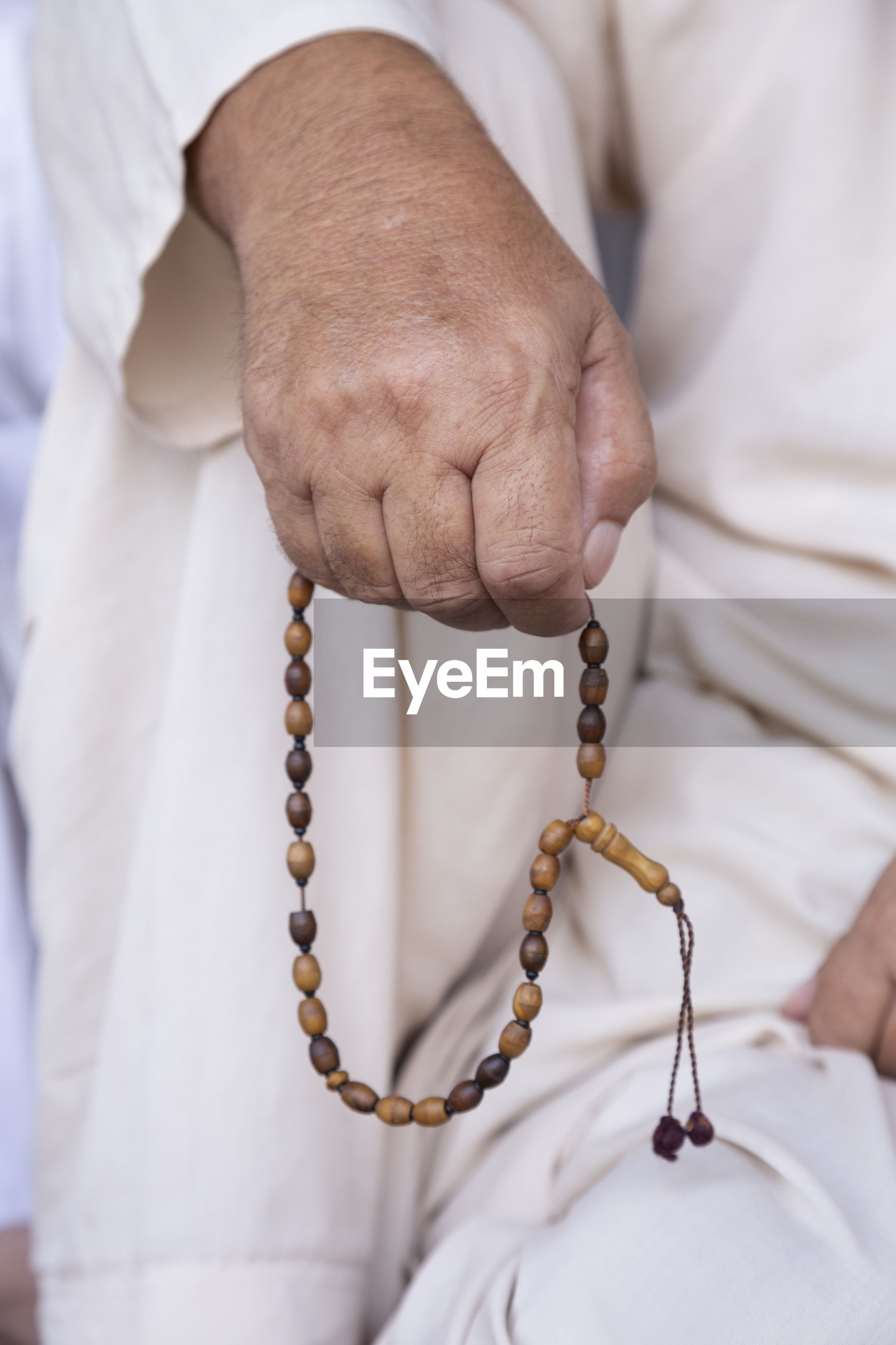 Midsection of man holding bead necklace while praying