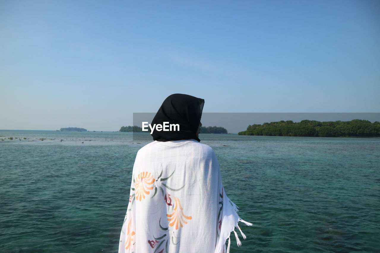 REAR VIEW OF WOMAN STANDING AT SEA SHORE AGAINST CLEAR SKY