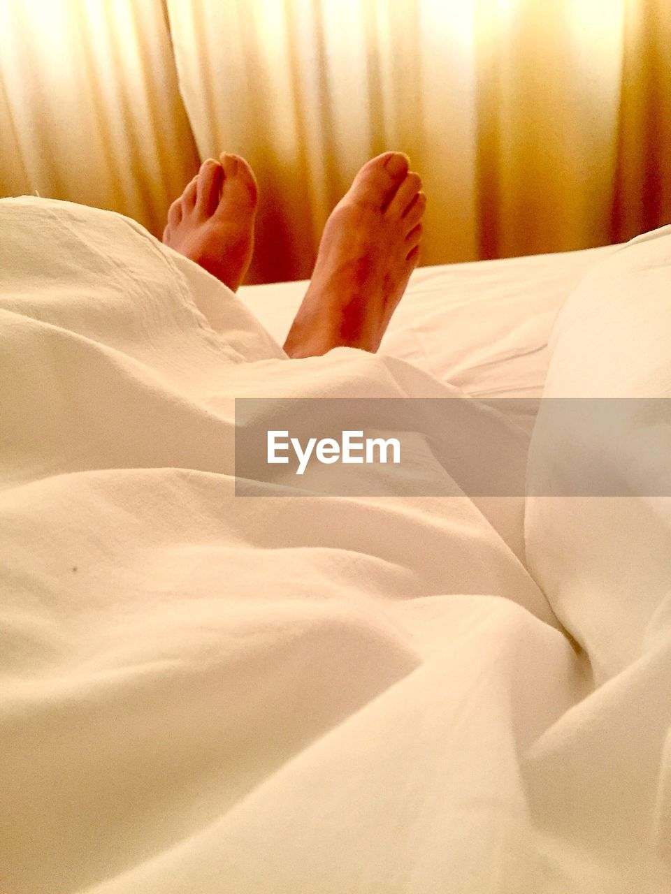 bed, bedroom, relaxation, comfortable, sheet, lying down, barefoot, low section, sleeping, resting, human foot, indoors, one person, real people, home interior, lifestyles, human leg, domestic room, pillow, close-up, day, people