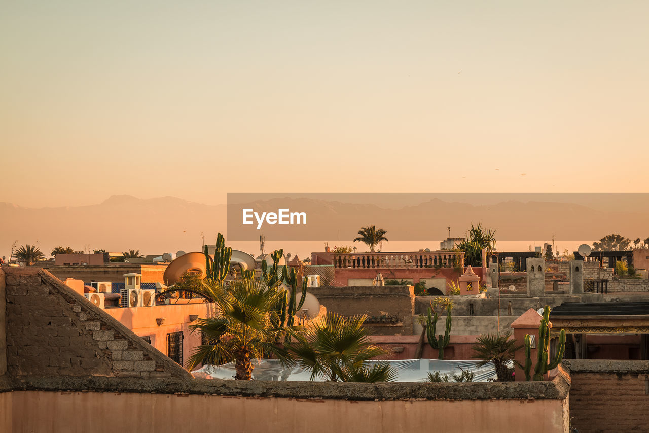 architecture, sky, building exterior, built structure, water, sunset, clear sky, copy space, building, nature, residential district, city, no people, orange color, waterfront, town, tree, outdoors, plant, townscape