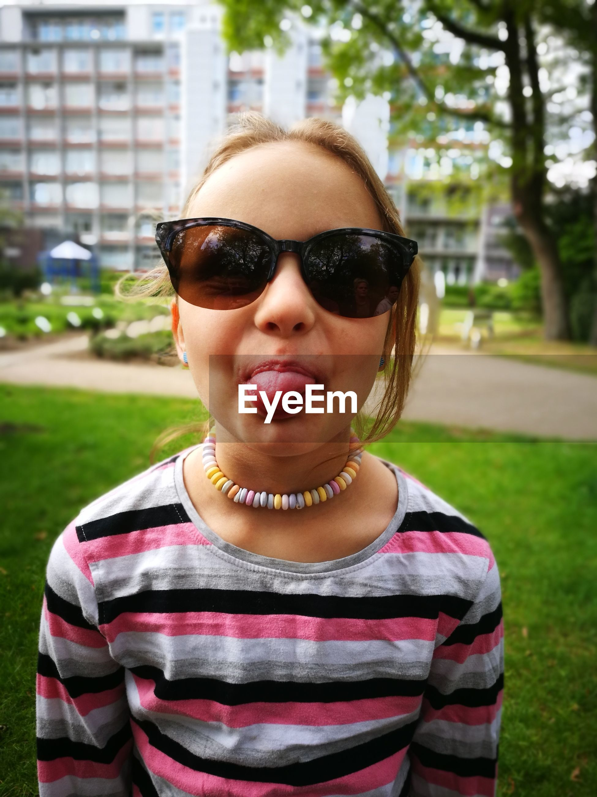 Portrait of girl wearing sunglasses sticking out tongue while standing in park