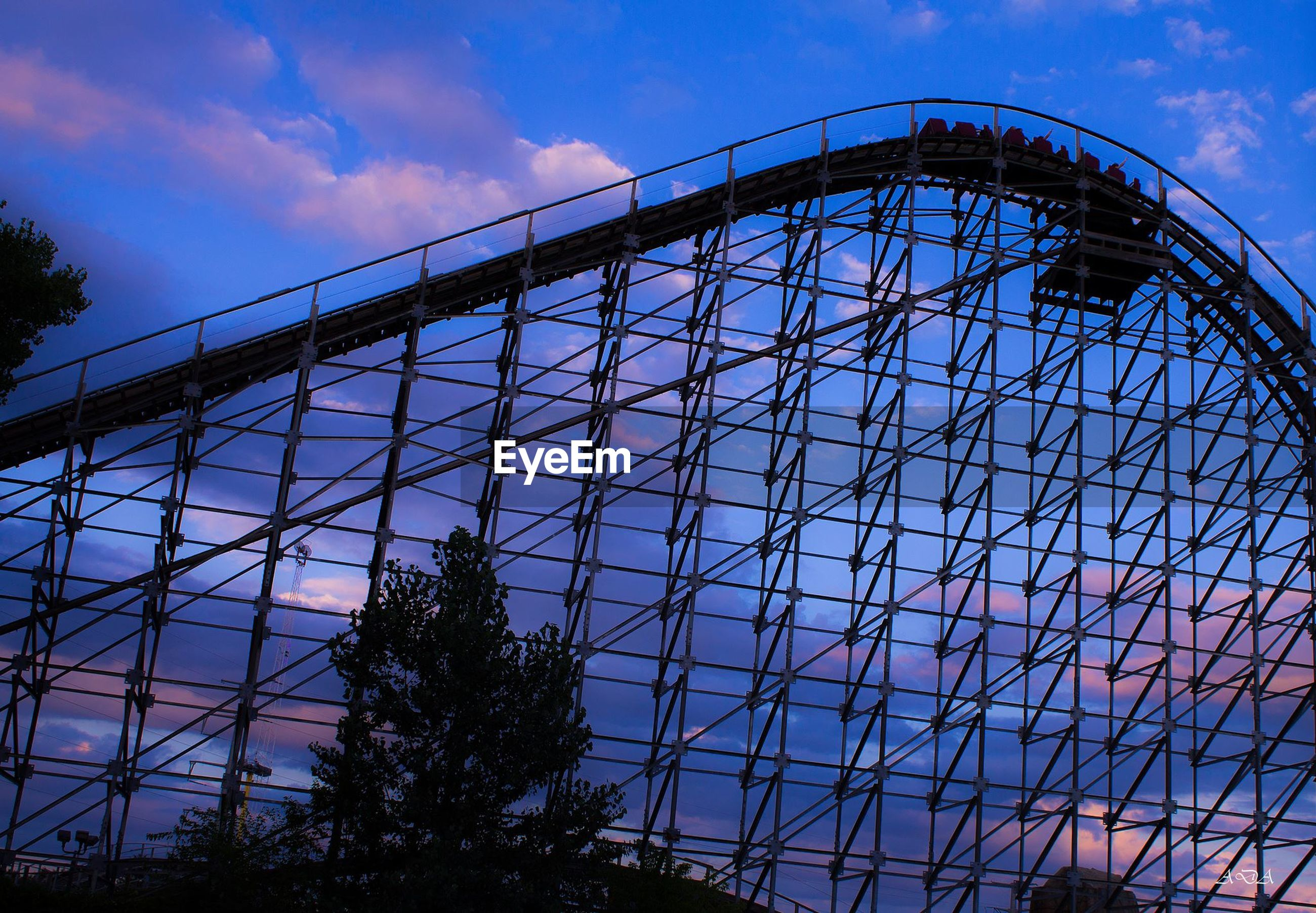 sky, low angle view, concentric, amusement park, tree, outdoors, no people, cloud - sky, rollercoaster, day