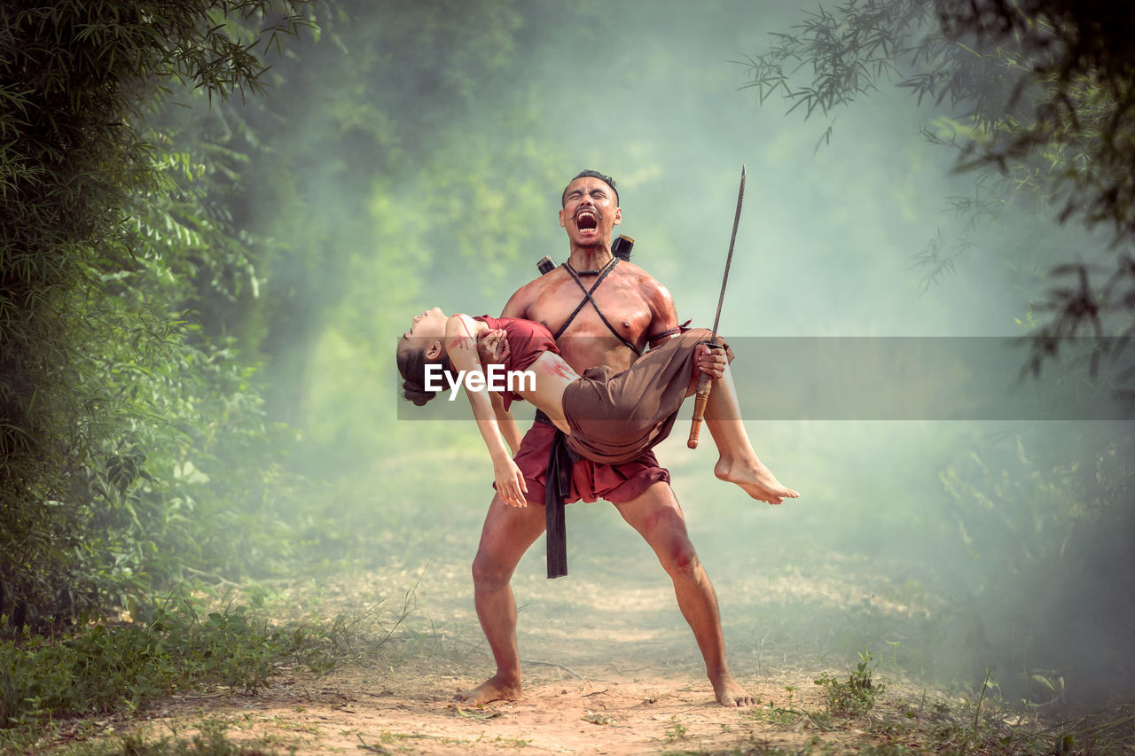 Full Length Of Shirtless Warrior Screaming While Carrying Dead Woman In Forest
