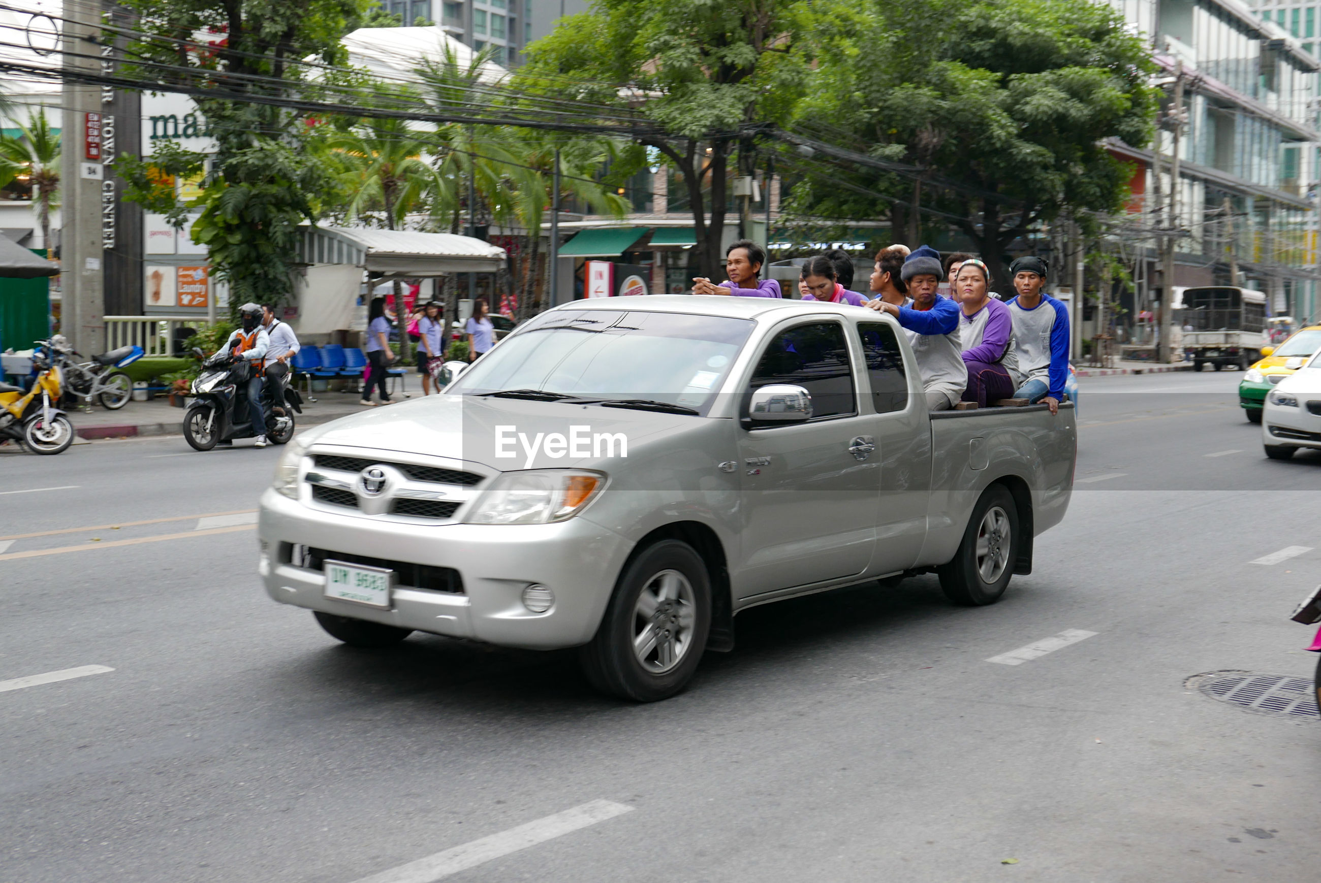 People traveling in pick-up truck on city street
