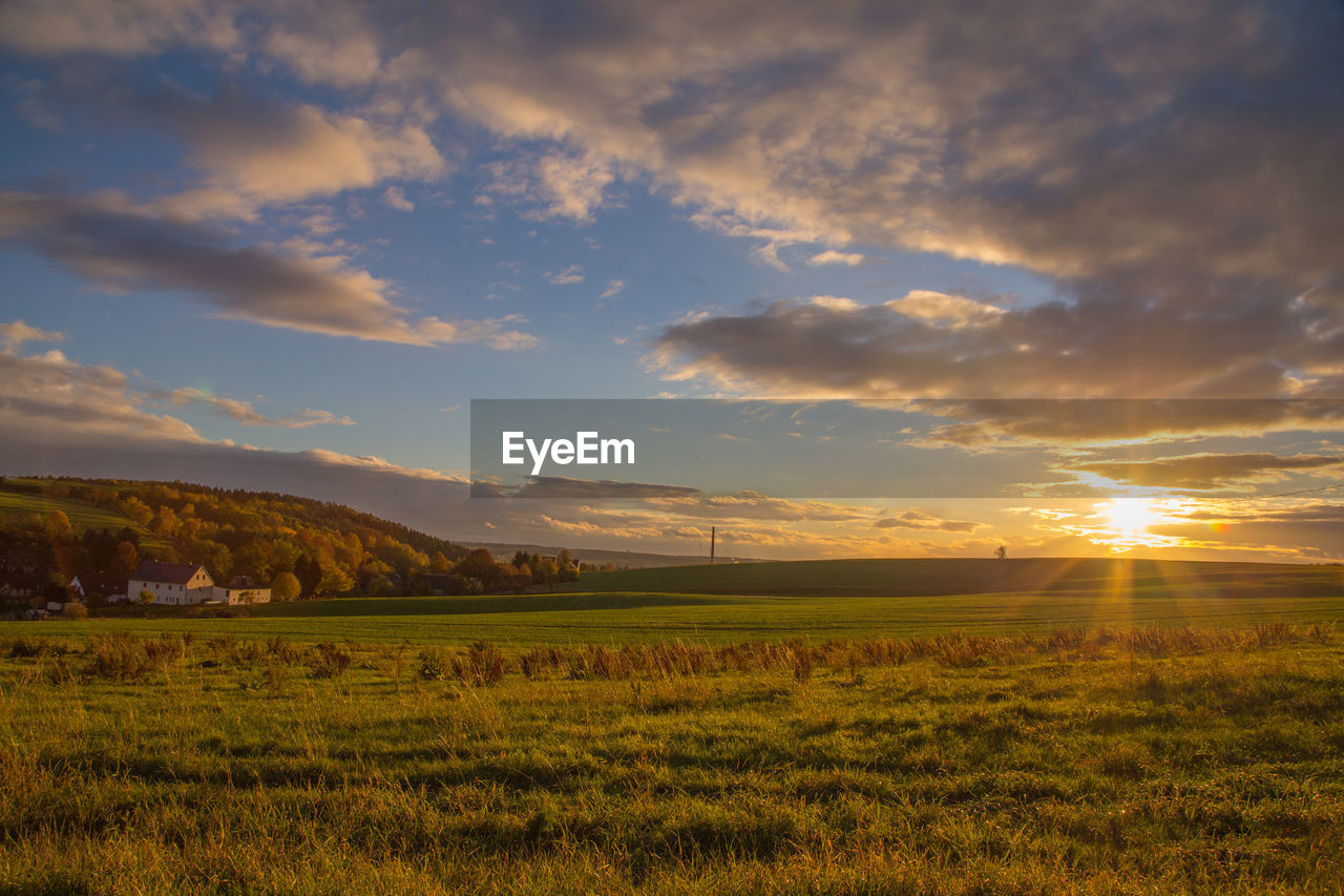 sky, cloud - sky, scenics - nature, beauty in nature, tranquility, tranquil scene, environment, landscape, field, land, sunset, plant, nature, grass, sunlight, idyllic, non-urban scene, growth, no people, green color, sun, outdoors
