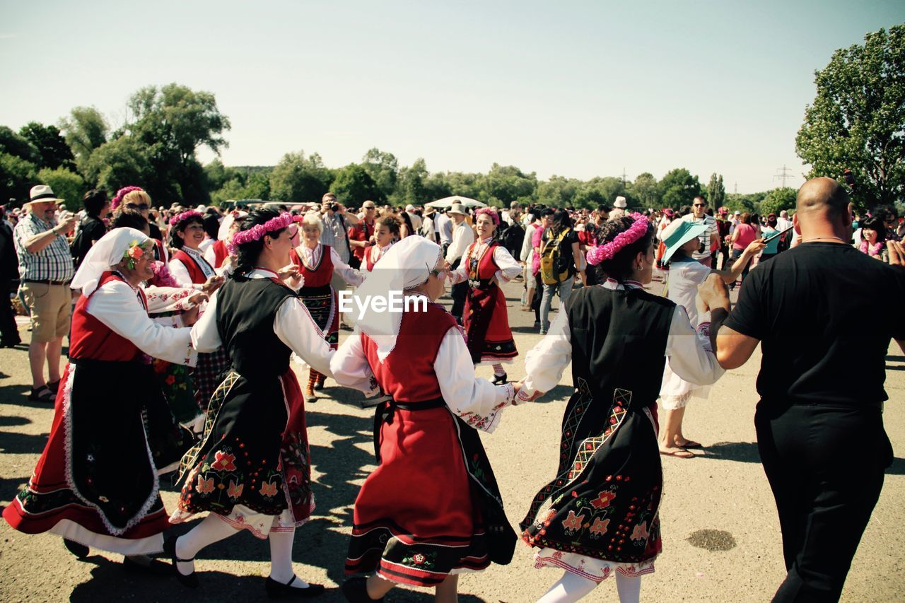 large group of people, togetherness, celebration, tree, real people, day, leisure activity, sunlight, men, outdoors, lifestyles, music, performance, crowd, clear sky, musician, people