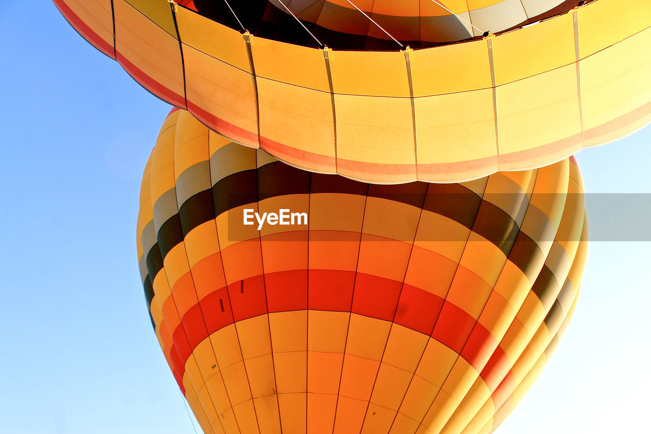 Low Angle View Of Orange Hot Air Balloons Against Clear Sky