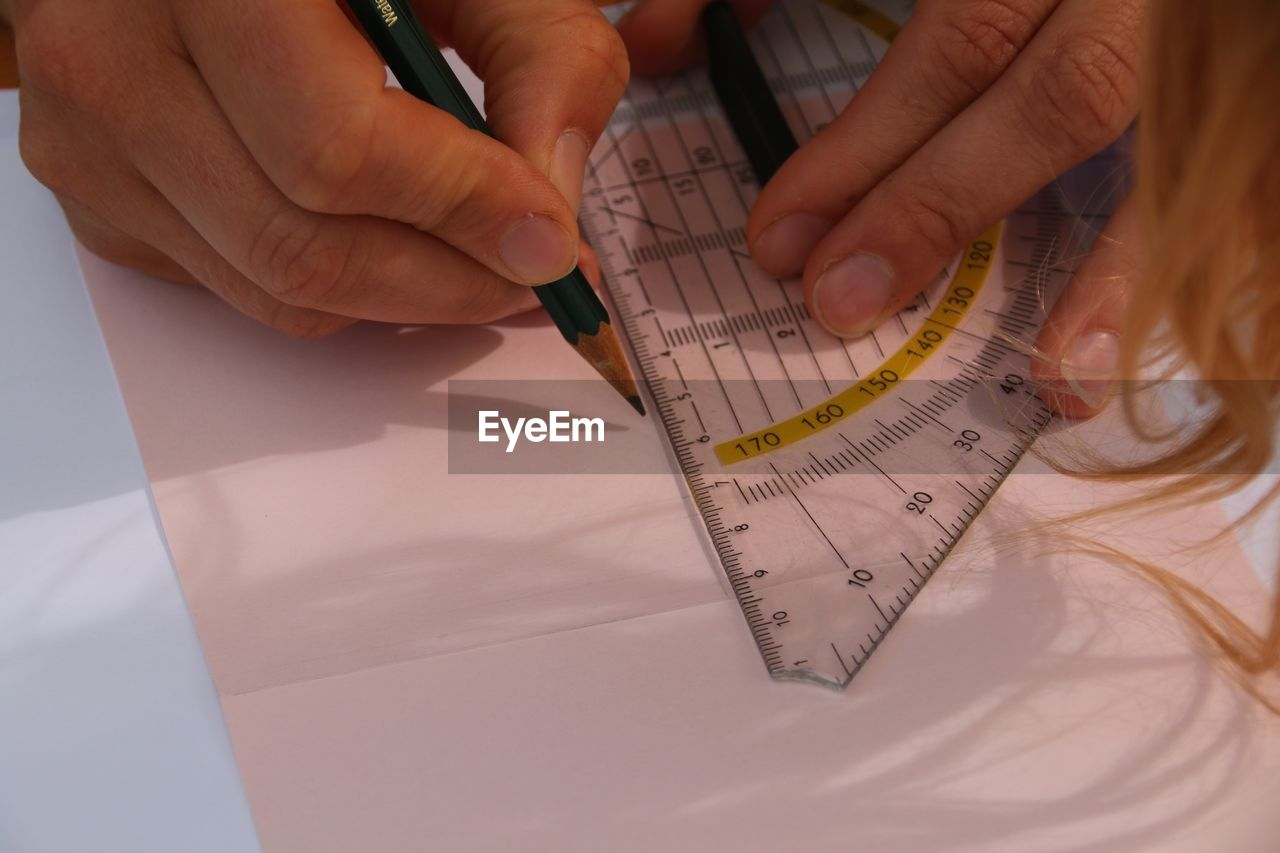Close-Up Of Woman Drawing Using Ruler On Paper