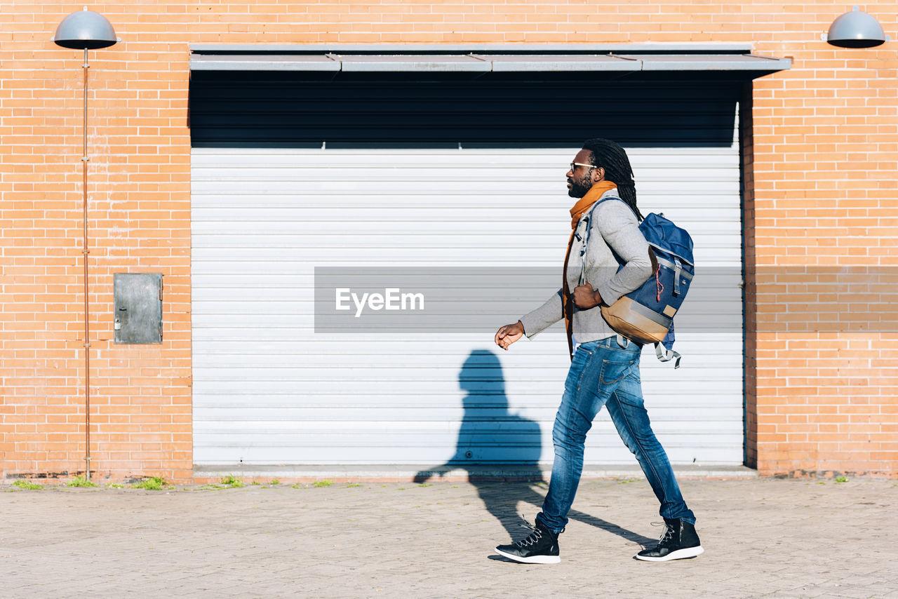 Full Length Of Man Walking By Shutter