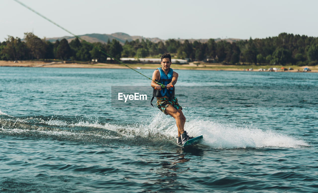 Full length of man doing wakeboard in a lake