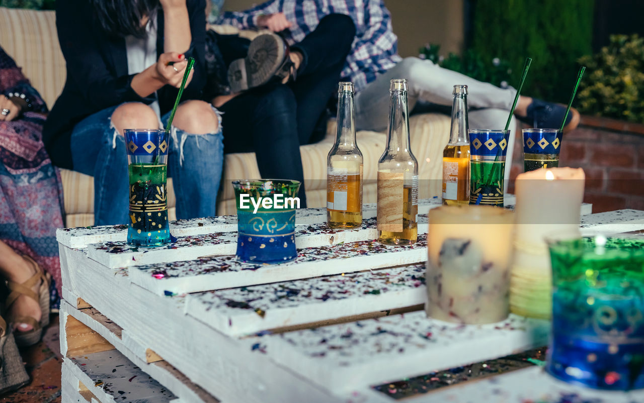 Drinks On Table By Friends Sitting On Sofa During Party