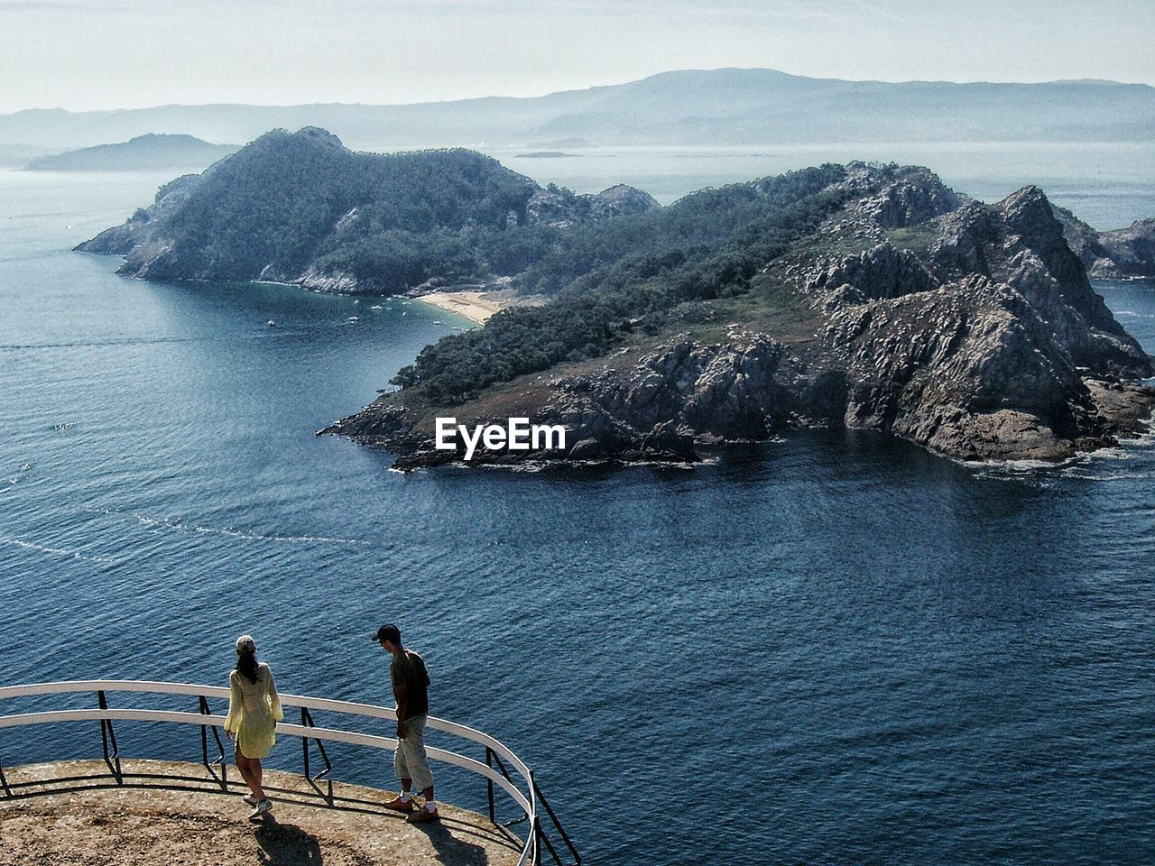 High Angle View Of Man And Woman At Observation Point By Sea