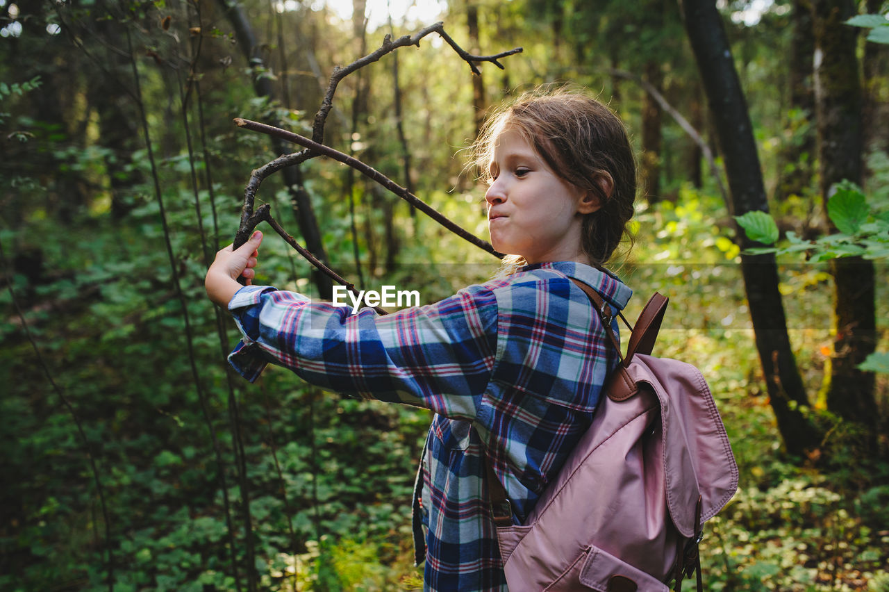 tree, plant, forest, land, one person, real people, leisure activity, nature, lifestyles, casual clothing, holding, focus on foreground, day, young adult, standing, looking, checked pattern, growth, woodland, outdoors, pre-adolescent child, hairstyle