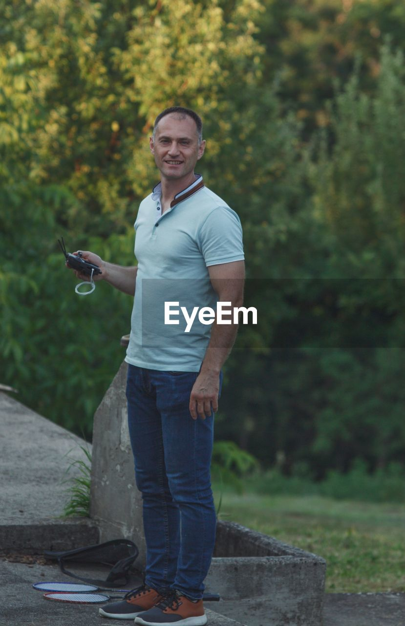 one person, looking at camera, portrait, casual clothing, wireless technology, mobile phone, real people, young men, full length, communication, smiling, standing, plant, lifestyles, men, day, young adult, holding, technology, outdoors, jeans