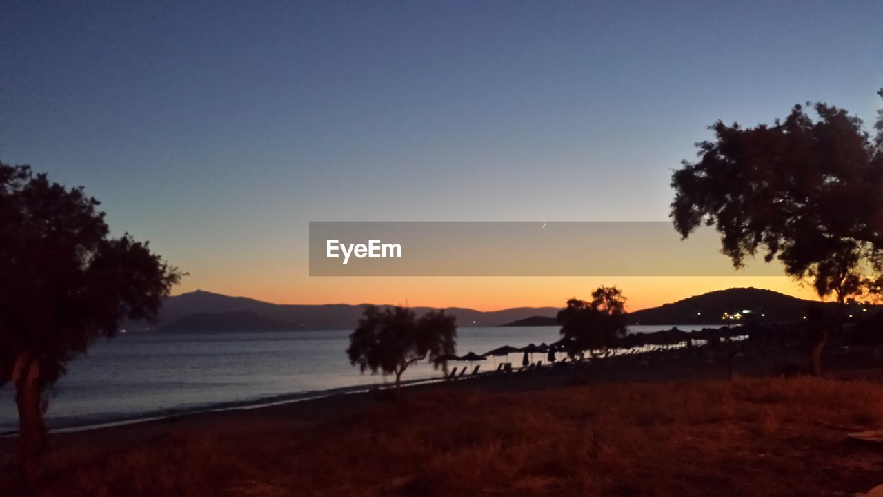 Scenic View Of Lake And Silhouette Trees Against Clear Sky During Sunset
