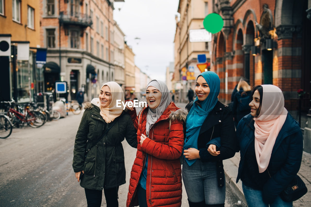 city, architecture, smiling, street, building exterior, young women, women, young adult, real people, city life, people, warm clothing, winter, lifestyles, adult, incidental people, happiness, clothing, emotion, city street, outdoors, scarf