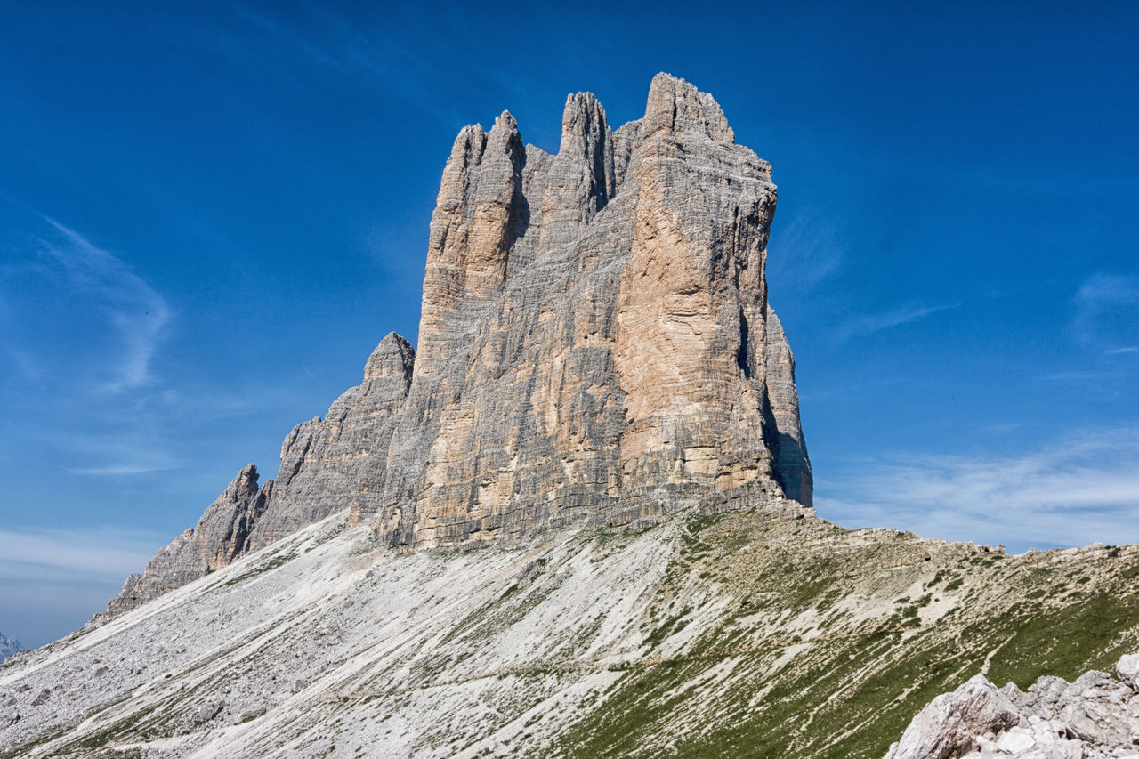 low angle view, day, rock - object, mountain, sky, nature, sunlight, outdoors, scenics, tranquility, beauty in nature, blue, no people, cliff