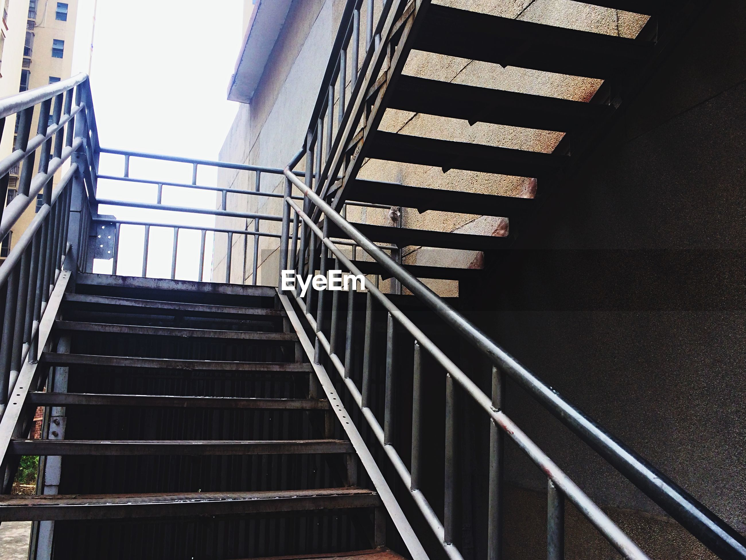 architecture, built structure, railing, staircase, steps, low angle view, steps and staircases, building exterior, building, pattern, modern, stairs, no people, day, diminishing perspective, city, metal, window, outdoors, wall - building feature