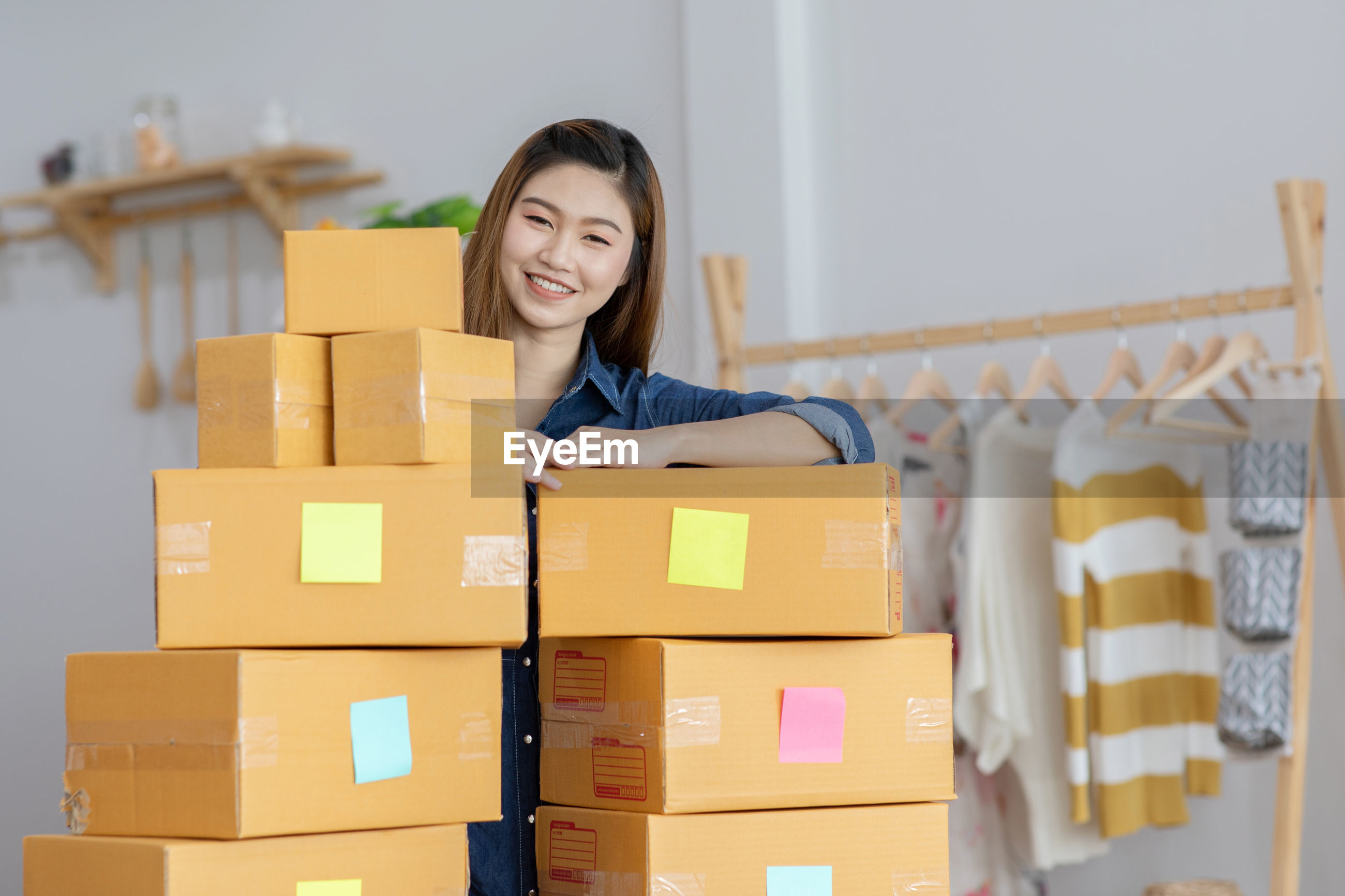 Portrait of smiling woman holding boxes
