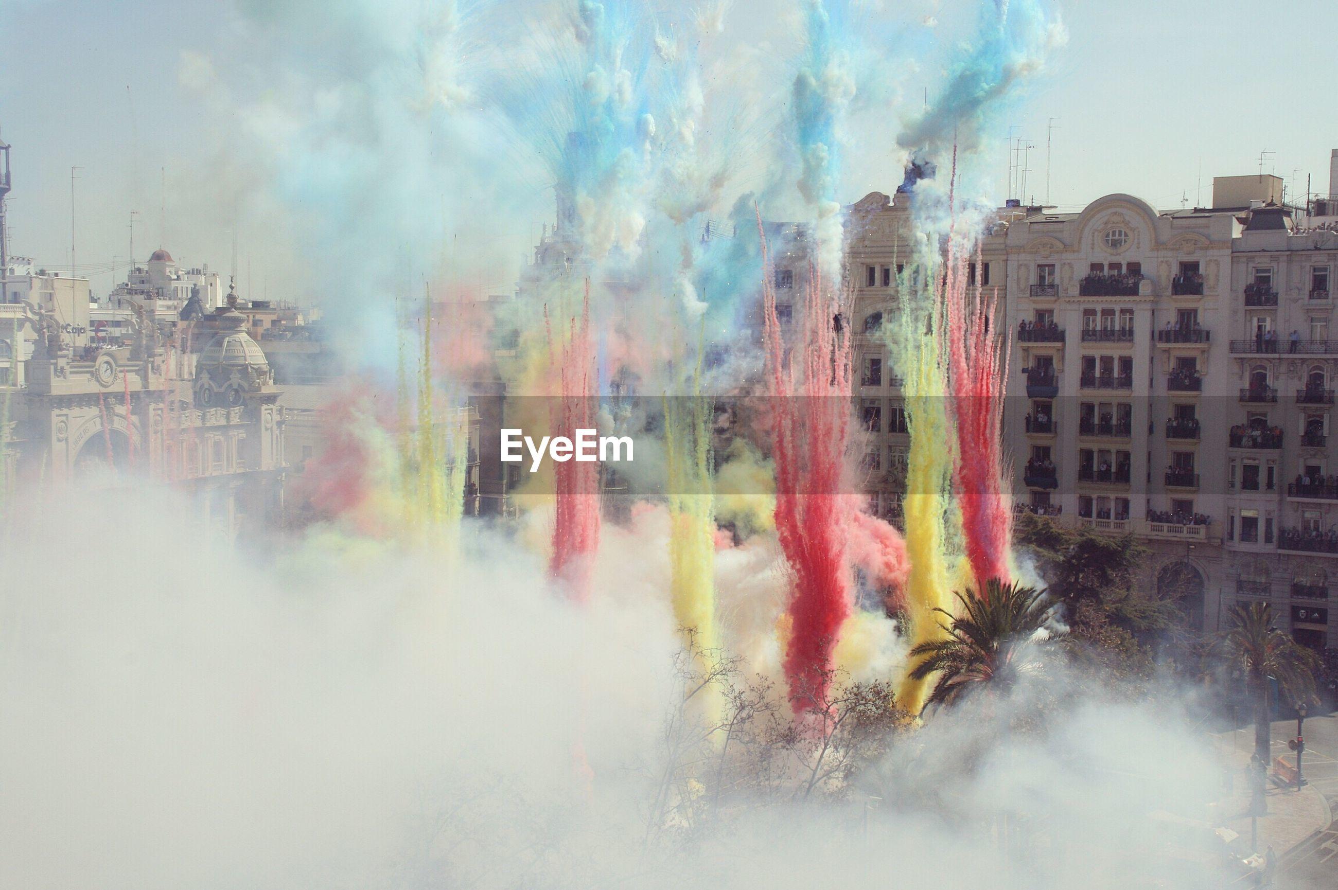 Rainbow over city against cloudy sky