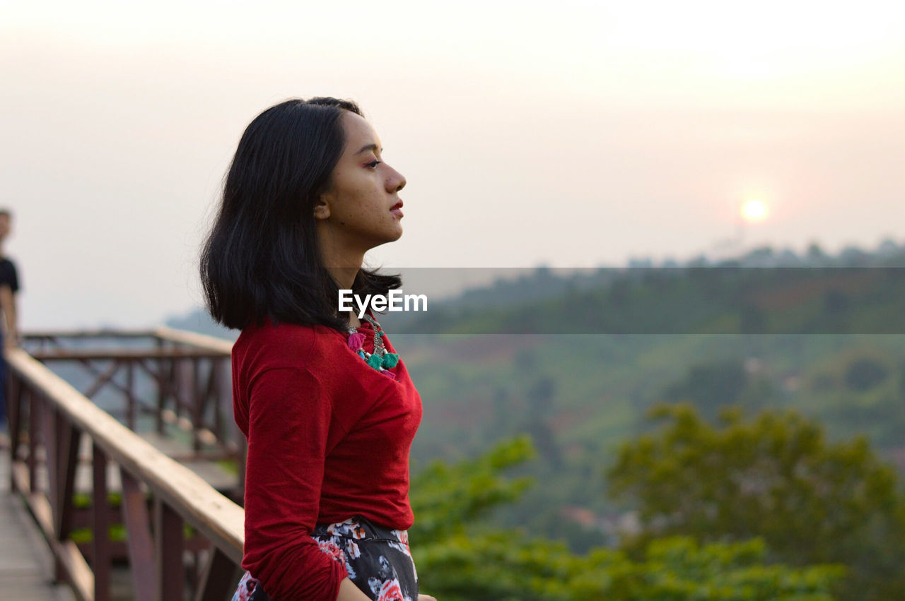 Profile view of young woman standing at observation point