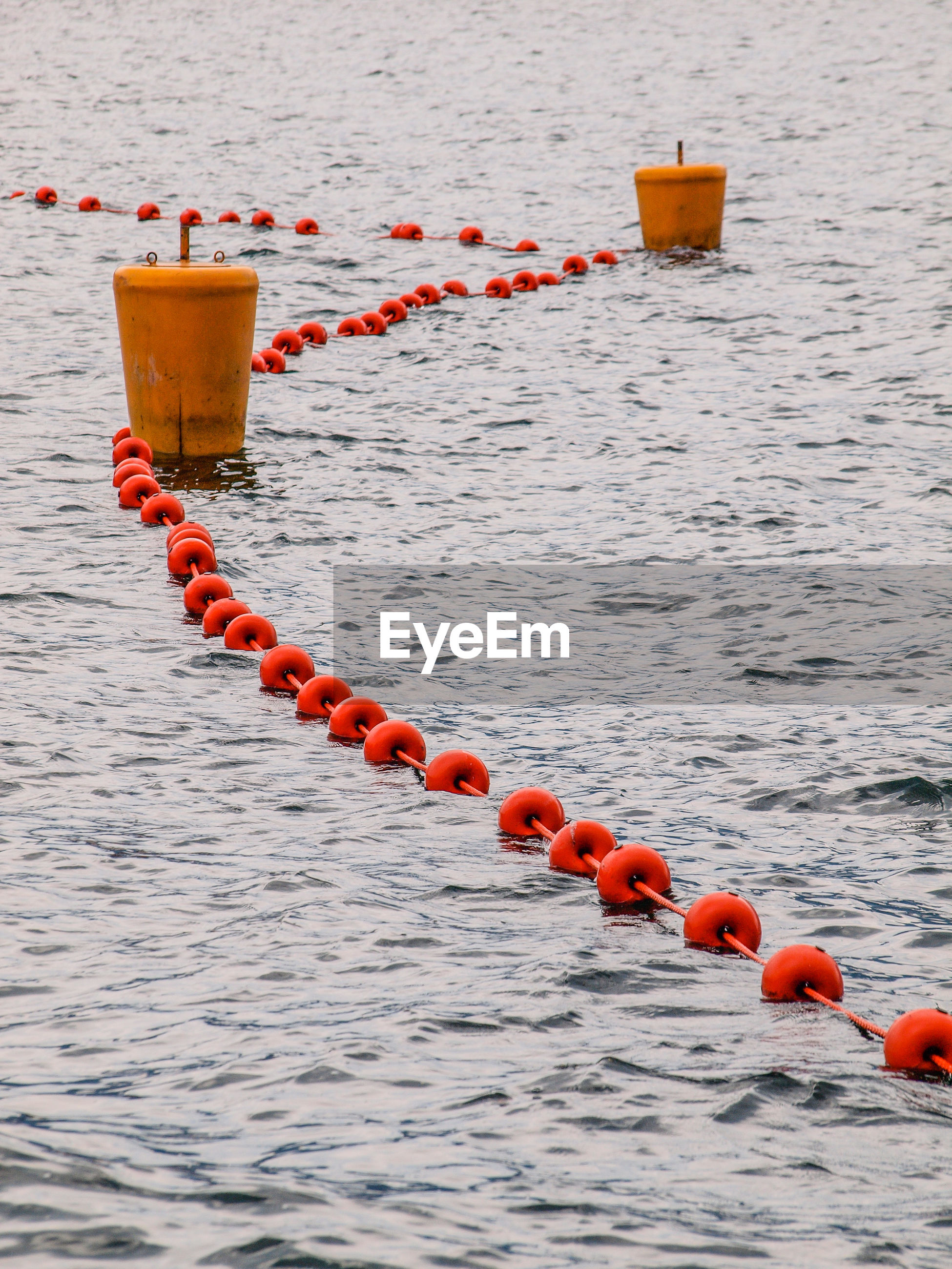 CLOSE-UP OF METALLIC FLOATING ON SEA