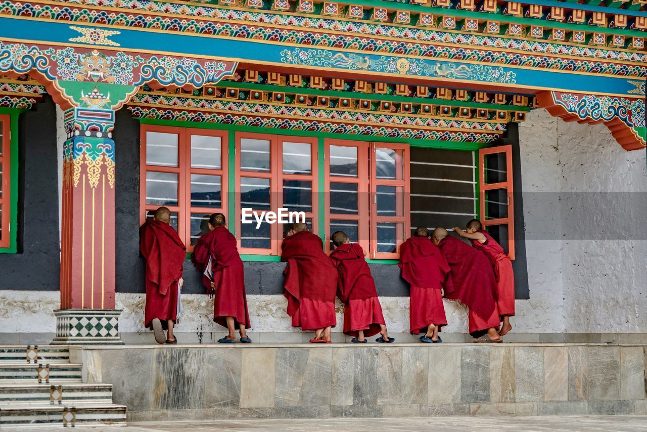 architecture, built structure, group of people, building, religion, building exterior, belief, spirituality, real people, place of worship, clothing, men, red, day, walking, people, traditional clothing, rear view, architectural column, outdoors, ornate