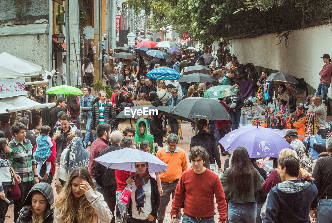 crowd, group of people, city, architecture, large group of people, umbrella, protection, street, real people, adult, walking, women, rain, wet, nature, built structure, security, outdoors, place