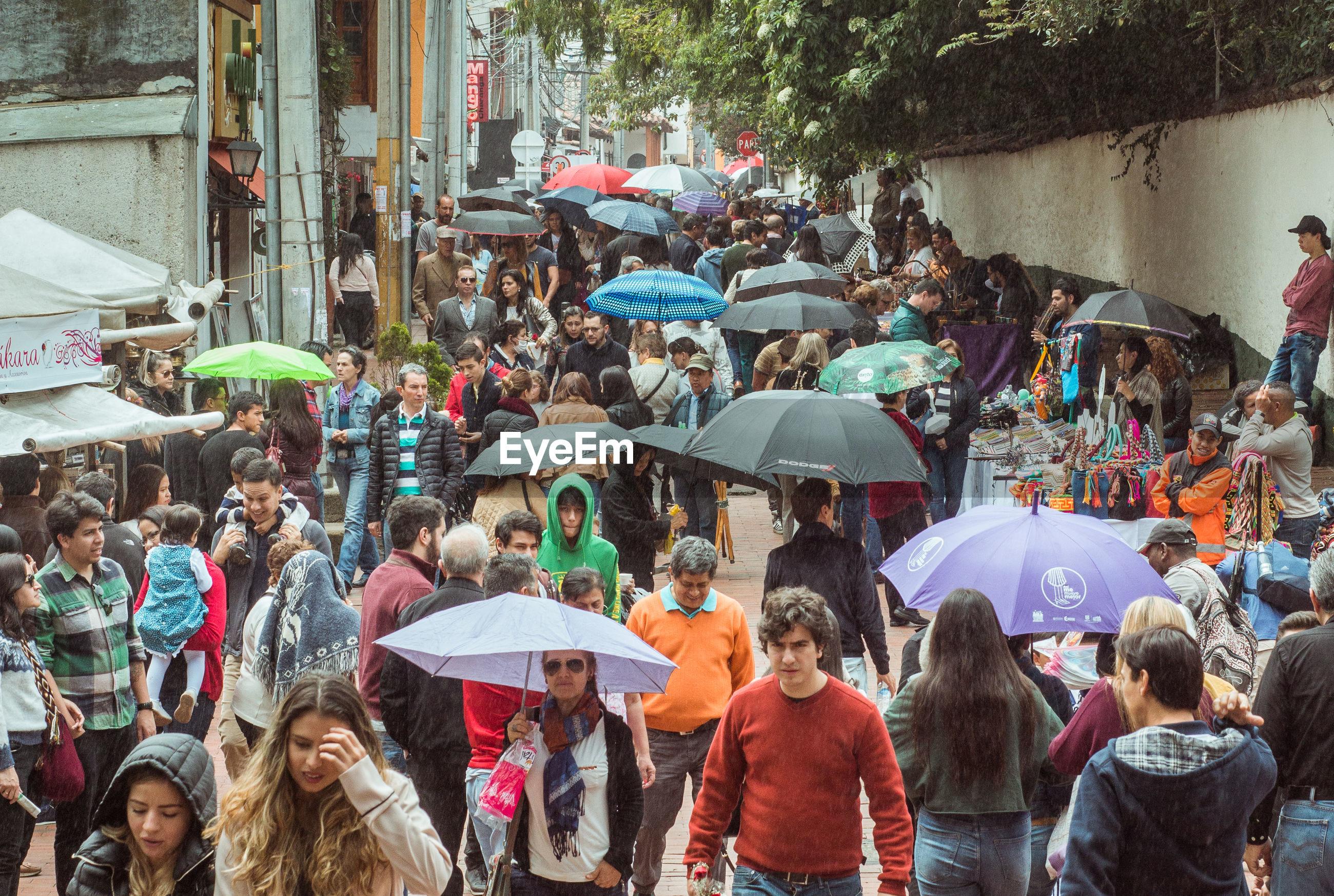 PEOPLE WALKING ON STREET IN RAIN