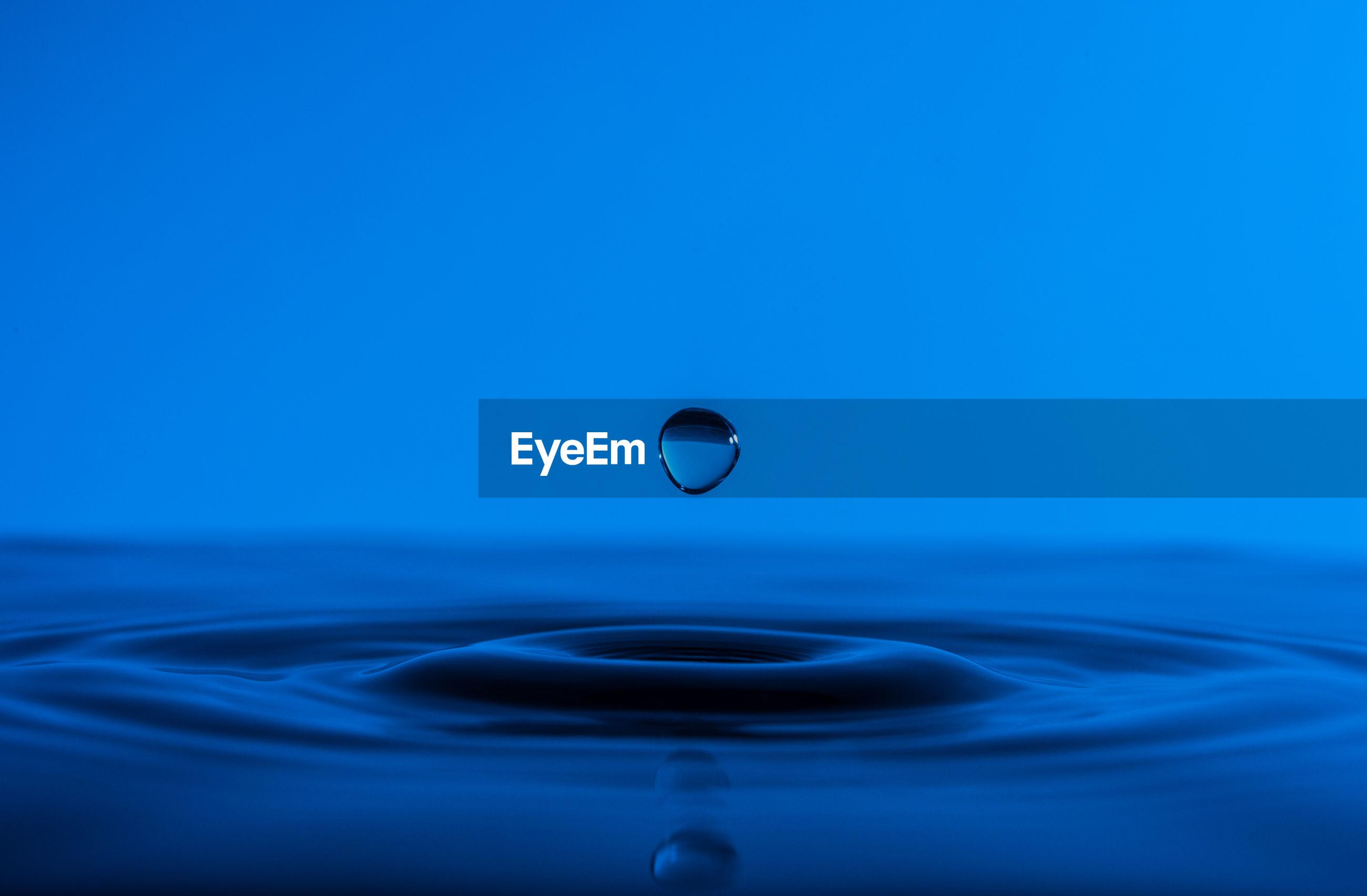MACRO SHOT OF WATER SPLASHING IN BLUE SEA
