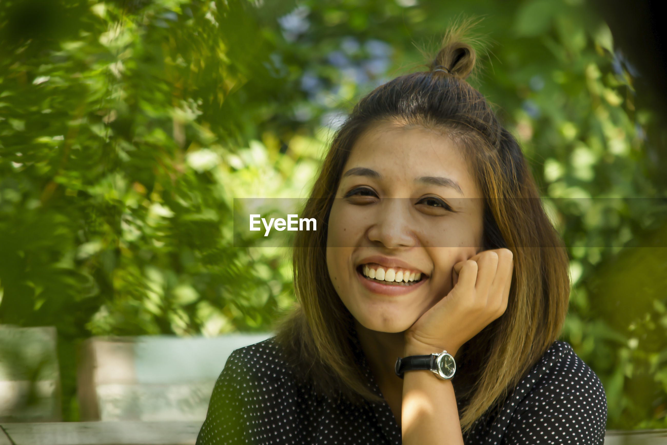 Close-up portrait of smiling woman against plants