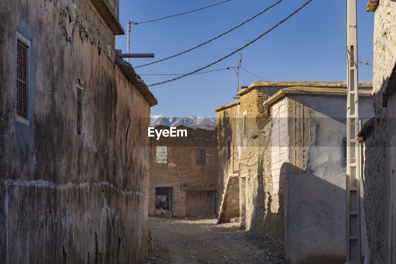 architecture, built structure, building exterior, building, sky, no people, city, nature, cable, residential district, house, clear sky, day, old, outdoors, the way forward, sunlight, direction, abandoned, road, alley
